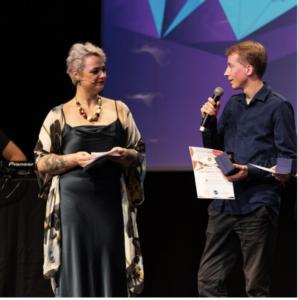 Adrian Wegener sprich auf einer Bühne, neben ihm steht eine elegant gekleidete ältere Dame die ihm zuhört.