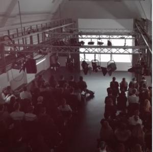 Ein großer Raum mit mehreren Studenten, sie hören einem Vortrag zu.