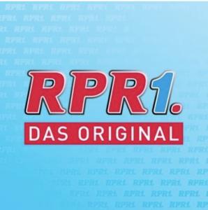 Das Logo von RPR1. Rote Schrift auf blauen Hintergrund.
