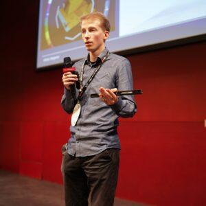 Adrian Wegener hält einen Eye Tracker während er auf einer Bühne spricht.